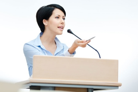woman_speaking_at_a_podiu_450