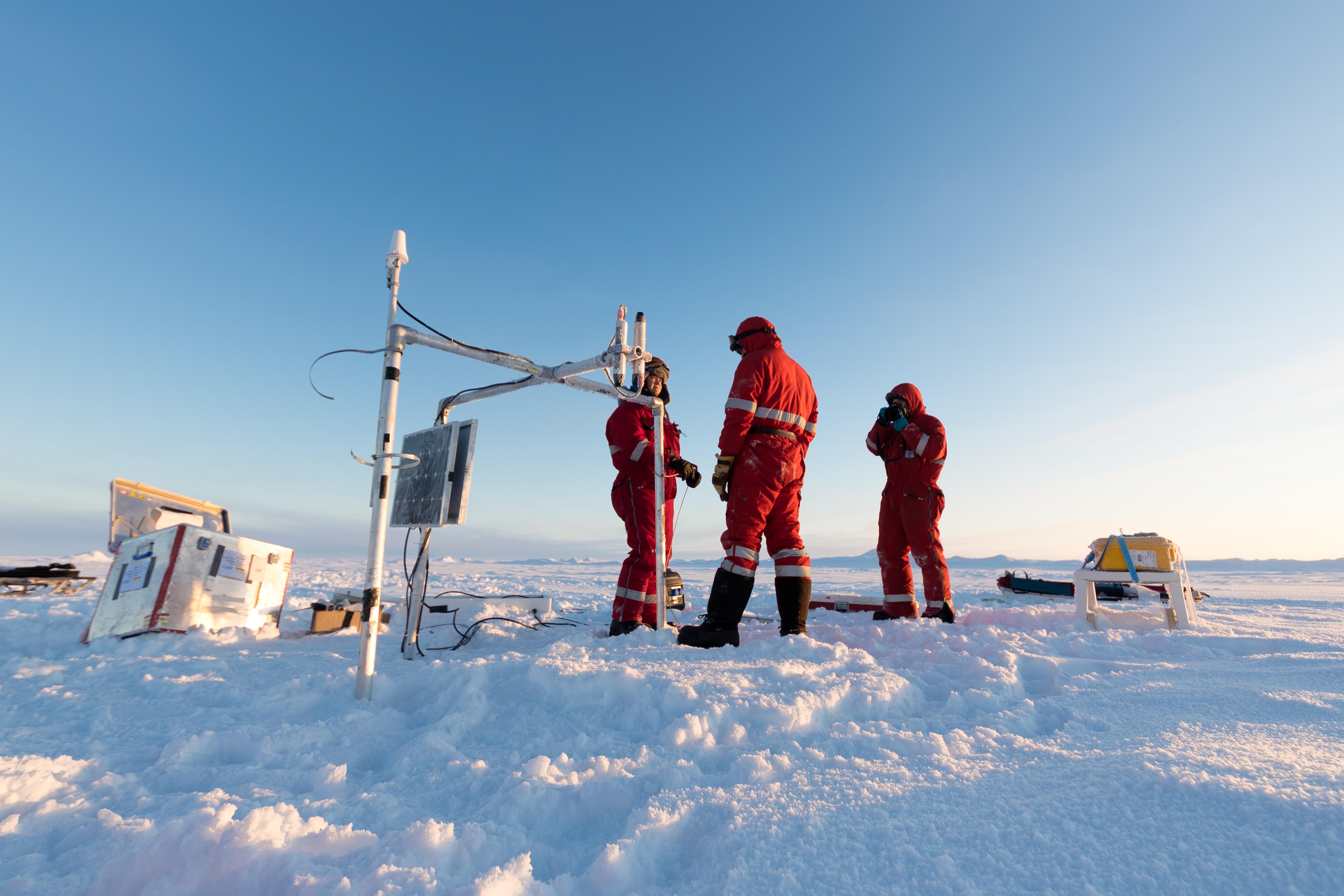 Forschergruppe bei der Arbeit auf dem Eis, Verankerung der Bojen, zur Bestimmung der Meereisdicke (Bildmitte) und der Schneedicke (Gelber Kasten,rechts)